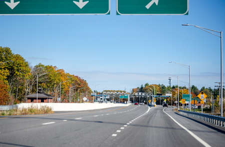 Wide divided turnpike highway with toll station with multi-line payment terminal for fast payment and working without transportation traffic delay in Maine New England Stock fotó