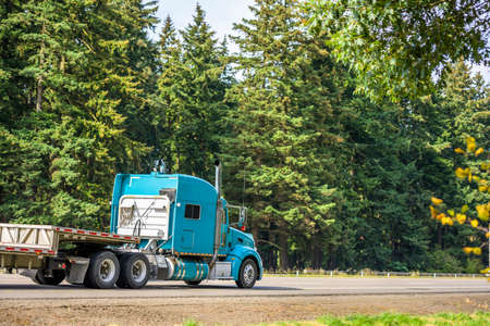 Bright blue long hauler big rig red industrial semi truck transporting empty step down semi trailer running on the straight highway road with green trees on the side to warehouse for next load