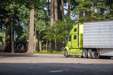 Bright green big rig industrial semi truck tractor with refrigerator semi trailer carry frozen food for delivery and running on the rest area parking lot with old trees to highway entrance