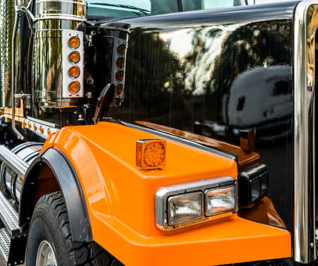 Front part of commercial freight transportation stylish black and orange big rig semi truck tractor with chrome accessories and glass headlight and reflecting shiny painted surface