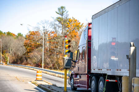 Powerful red big rig industrial diesel semi truck with dry van semi trailer transporting cargo standing on the highway entrance with traffic light with colorful maples autumn trees in New England Stock fotó