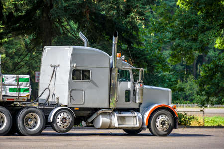 Classic white long hauler big rig industrial semi truck tractor with sleeper cab compartment for truck driver rest and loaded flat bed semi trailer standing on the rest area parking lot