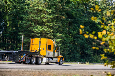 Bright yellow long hauler big rig red industrial semi truck transporting empty step down semi trailer running on the straight highway road with green trees on the side to warehouse for next load