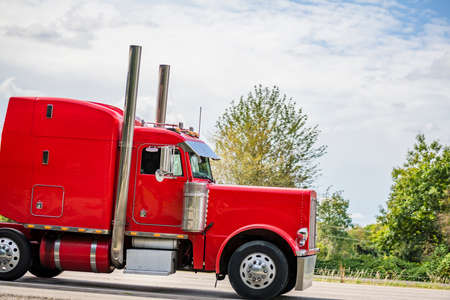 Profile of the powerful bright classic red big rig semi truck tractor with vertical exhaust chrome pipes and truck driver resting compartment running on the green highway road