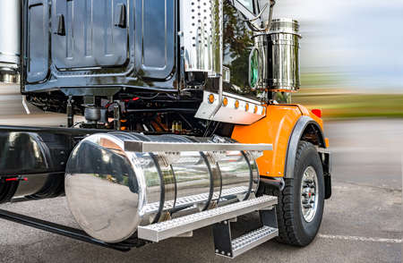 Powerful shiny big rig semi truck tractor in black and orange with polisher aluminum fuel tanks and steps and another accessories ready to go for industrial heavy freight