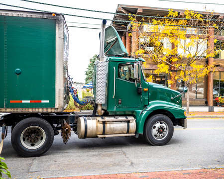 Industrial green big rig day cab semi truck tractor with roof spoiler transporting commercial cargo in dry van semi trailer moving on the small city street road with buildings in New England