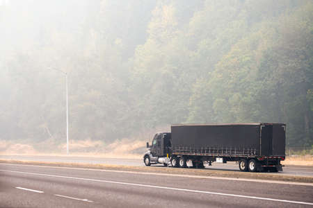 Black stylish industrial grade big rig semi truck with covered dry van semi trailer transporting commercial cargo driving on the unhealthy road in the thick smog from a disaster extensive forest fire