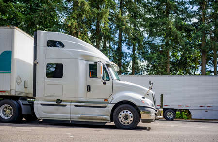 Light gray long haul industrial big rig semi truck tractor with powerful grille guard and with dry van semi trailer standing on the rest area parking lot parallel to the highway for take a break