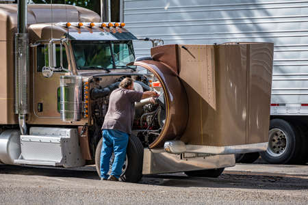 Experienced truck driver checking engine for properly work during a rout on brown classic industrial grade professional big rig diesel semi truck standing on rest area with open hood Stock fotó
