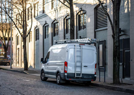 Compact commercial cargo mini van for delivery and small business services standing with ladder on the roof on the urban city street with multilevel apartments buildings