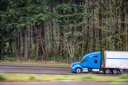 Big rig industrial blue semi truck with turned on headlights transporting cargo in dry van semi trailer running on the twilight wet road with forest background in rain weather