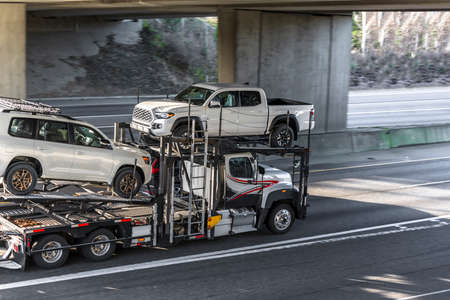 Big rig white car hauler semi truck transporting cars on the two level hydraulic modular semi trailer