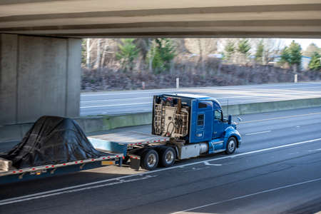 Classic big rig industrial blue semi truck tractor with low roof cab and sleeping compartment transporting covered cargo on step down semi trailer running on the wide highway road with bridge