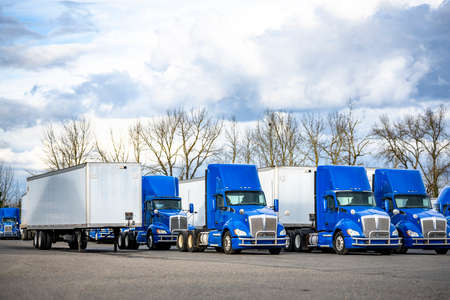 Team of professional commercial day cab blue big rig semi trucks tractors and dry van semi trailers standing at row on industrial parking lot waiting for next freight route 版權商用圖片