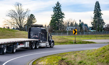 Classic black long haul American big rig bonnet semi truck tractor with empty flat bed semi trailer turning on the round highway entrance between two hills going to warehouse for the next load