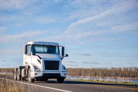 Powerful Big rig white day cab semi truck tractor without semi trailer running on the narrow highway road along the river to warehouse for pick up the next loaded trailer for delivery