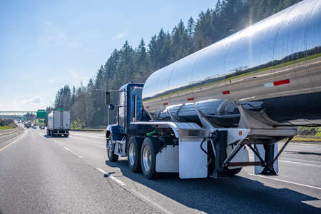 Commercial big rig blue industrial long haul semi truck transporting liquid cargo in tank semi trailer driving on the multiline interstate highway road with one way traffic direction