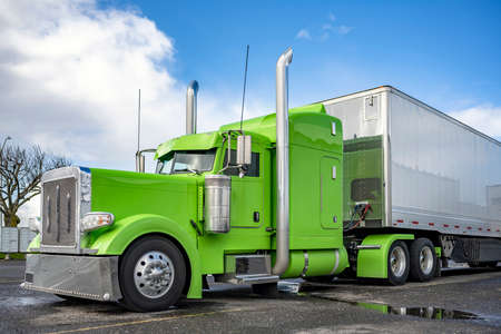 Power green classic American Idol big rig semi truck tractor with shiny chrome parts and high vertical exhaust pipes and dry van semi trailer standing on the parking lot waiting for the next load 版權商用圖片