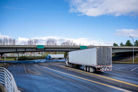 Two Big rigs industrial semi trucks transporting cargo in dry van semi trailers driving towards each other on the wide road intersection with different traffic directions and overpass bridge