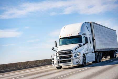 Commercial big rig white industrial long haul semi truck transporting frozen cargo in refrigerator semi trailer driving on the multiline interstate highway road with one way traffic direction 版權商用圖片