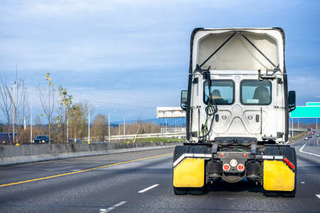 Powerful Big rig white high cab semi truck tractor without semi trailer running on the multiline divided wide highway road to warehouse for pick up the next loaded trailer for delivery Zdjęcie Seryjne