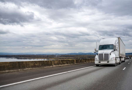 Commercial big rig white industrial grade long haul professional semi truck transporting cargo in dry van semi trailer moving on the divided interstate highway road with one way traffic direction
