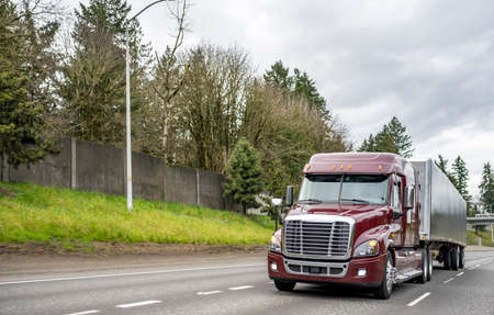 Commercial big rig Burgundy industrial grade long haul professional semi truck transporting cargo in dry van semi trailer moving on the divided interstate highway road with one way traffic direction 版權商用圖片