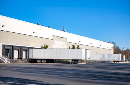 Team of professional freight commercial dry van semi trailers without industrial big rig semi trucks standing at row on business parking lot loading cargo at warehouse dock gates
