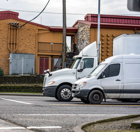 Commercial day cab white big rig semi truck with dry van semi trailer running beside the compact cargo mini van on the city street with crossroad driving for goods deliveries 版權商用圖片