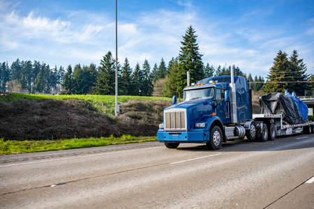 Huge blue classic big rig industrial semi truck transporting covered with tarp heavy commercial cargo on step down semi trailer running on the wide highway road with trees on the side