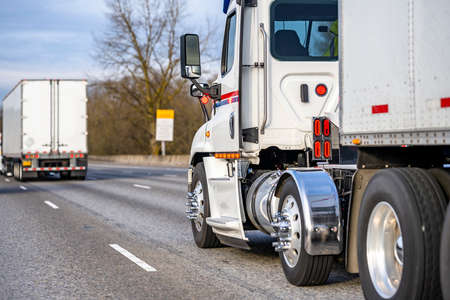 White day cab big rig industrial semi truck transporting commercial cargo in dry van semi trailer running in convoy behind another semi truck driving on the interstate highway road