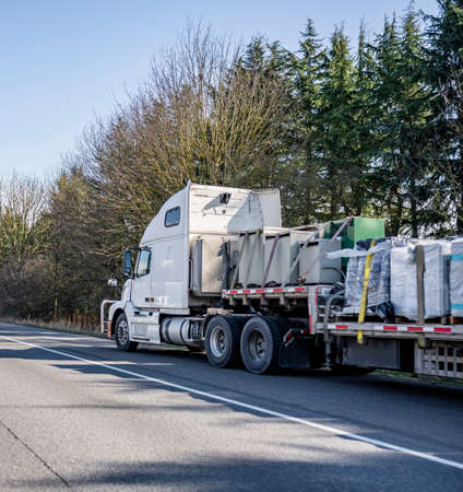 Classic white loaded big rig semi truck with secured with slings commercial cargo on step down semi trailer standing on the road shoulder out of service waiting for mobile repair help 版權商用圖片
