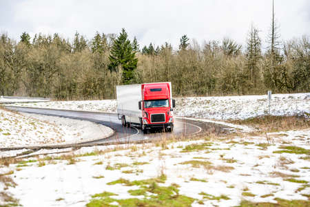 Commercial big rig long haul red semi truck transporting commercial cargo in dry van semi trailer turning on the exit from highway road between hills covered with snow