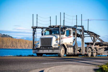 Classic Big rig industrial car hauler semi truck with empty double deck hydraulic modular semi trailers running on the narrow road along the river to warehouse for pick up next cars load