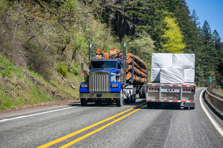 Different classic loaded big rigs semi trucks with semi trailers moving in opposite directions on the narrow winding road with green forest on the side at national Columbia Gorge Area
