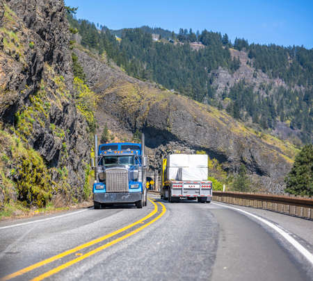 Different classic loaded big rigs semi trucks with semi trailers moving in opposite directions on the narrow winding road with tunnel and rock on the side at national Columbia Gorge Area
