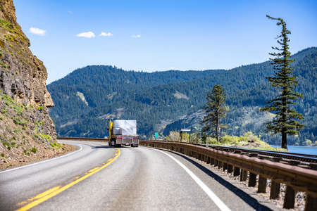Bright yellow classic big rig semi truck transporting flat bed semi trailer loaded with covered lumber cargo turning on the winding highway road at national Columbia River Gorge with rock mountain 版權商用圖片