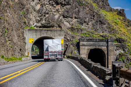 Powerful classic big rig semi truck transporting flat bed semi trailer loaded with covered lumber cargo turning on the winding highway road through a tunnel in the rock at Columbia River Gorge