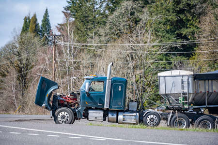 Broken industrial big rig semi truck tractor with an open hood and loaded bulk semi trailer stands on the side of the road waiting for a mobile repair crew or a tow tractor for towing to repair shop