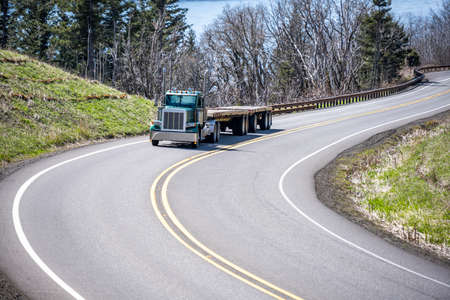 Powerful industrial day cab dark green classic big rig semi truck tractor with two empty flat bed semi trailers running on the winding mountain road at Columbia Gorge to warehouse for next load