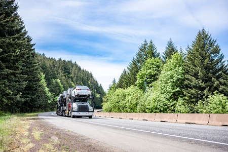 White compact big rig industrial car hauler semi truck transporting cars on the hydraulic modular two level semi trailer running on curving highway road with green mountain forest in Columbia Gorge 版權商用圖片