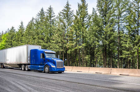 Blue big rig long haul industrial semi truck tractor transporting cargo in dry van semi trailer running on curving highway road with protective fence and green mountain forest in Columbia Gorge