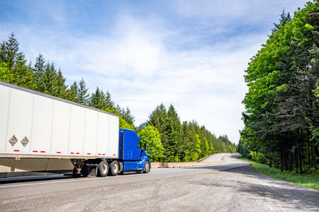 Blue big rig long haul industrial semi truck tractor with roof spoiler transporting cargo in dry van semi trailer running on curving highway road with green forest and mountain in Columbia Gorge