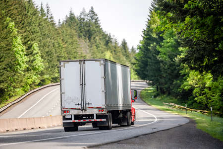 Red big rig long haul industrial semi truck tractor transporting cargo in dry van semi trailer running on curving highway road with protective fence and green mountain forest in Columbia Gorge Stockfoto