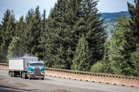 Old style cab over big rig industrial semi truck tractor transporting dusty cargo in covered low profile bulk semi trailer running on curving highway road with green mountain forest in Columbia Gorge