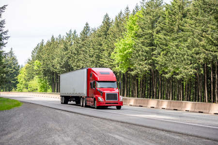 Red big rig long haul industrial semi truck tractor transporting cargo in dry van semi trailer running on curving highway road with protective fence and green mountain forest in Columbia Gorge