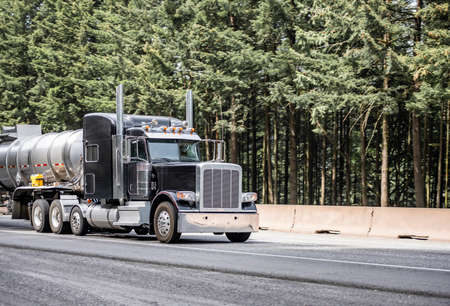 Black classic big rig industrial semi truck tractor transporting liquid cargo in stainless steel tank semi trailer running on curving highway road with green mountain forest in Columbia Gorge