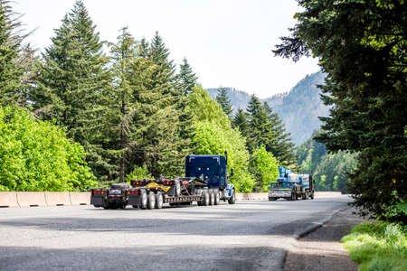 Two big rig industrial semi truck tractors transporting commercial cargo on step down semi trailers running at same direction convoy on highway road with green forest trees in Columbia Gorge