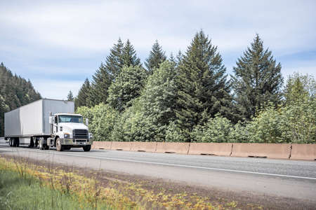 White day cab big rig industrial semi truck tractor for local deliveries transporting commercial cargo in dry van semi trailers running on highway road with green forest trees in Columbia Gorge