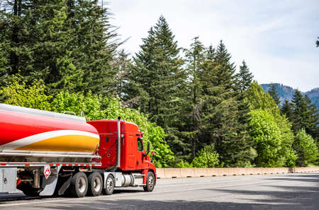 Red low profile big rig industrial semi truck tractor transporting liquid cargo in red tank semi trailer running on curving highway road with green mountain forest in Columbia Gorge